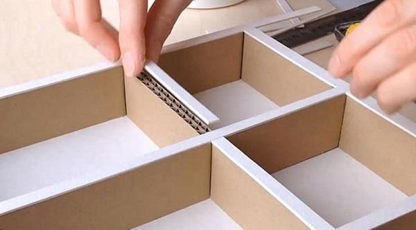 Dán trang trí che phủ các phần nối của kệ để hoàn thành cách làm tủ bằng giấy